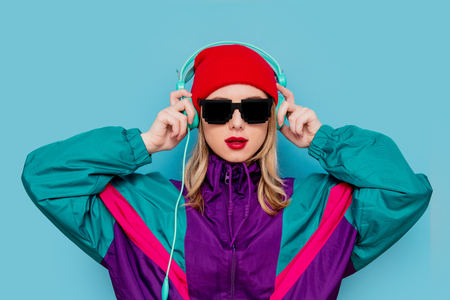 Portrait of a woman in red hat, sunglasses and suit of 90s with headphones on blue background. Banque d'images - 119801262