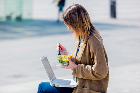 Young businesswoman eating salad and working with computer at urban outdoor. Dinner time concept Banco de Imagens