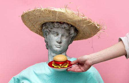 Antique bust of male in hat with hamburger on pink background. Ready for summer vacation Stock Photo