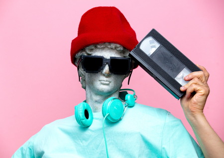 Antique bust of male in hat with headphones and VHS cassette on pink background. Ready for summer vacation