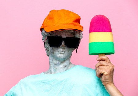 Antique bust of male in hat with sunglasses and toy ice-cream on pink background. Ready for summer vacation Stock Photo