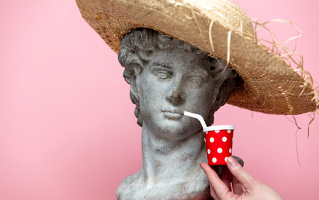 Antique bust of male in hat with cola drink on pink background. Ready for summer vacation