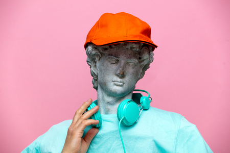 Antique bust of male in cap with headphones on pink background. Ready for summer vacation