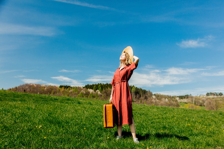 Beautiful girl in red dress and hat with suitcase on meadow. Spring season