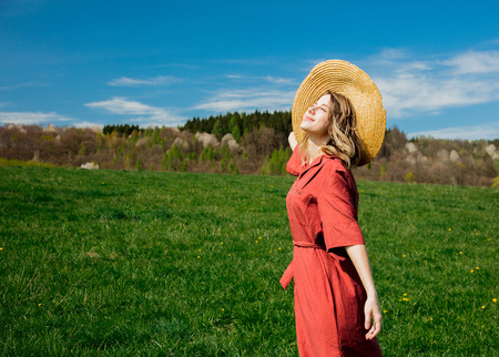 Beautiful girl in red dress and hat have a carefree time on meadow in mountains with forest on background. Spring season
