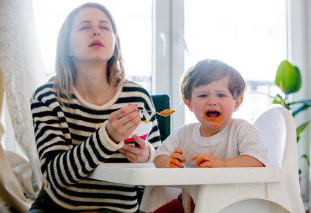 Young mother feeding a toddler boy with a spoon and dog looking on it