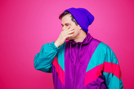 Style white man in 90s jacket and purple hat on purple-pink background 免版税图像