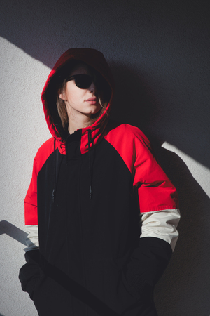 Style girl in jacket with hood stay on balcony with shadows.