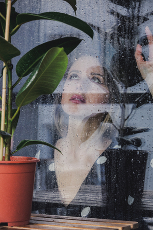 young sad woman near wet window after the rain misses the ficus plant standing outside the window. 版權商用圖片