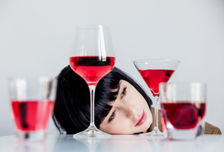 Brunet woman near glasses of wine on a table and white background Imagens