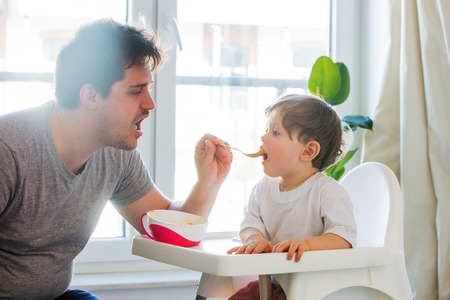 Young father try to feeding a toddler boy with a spoon in a chair 版權商用圖片