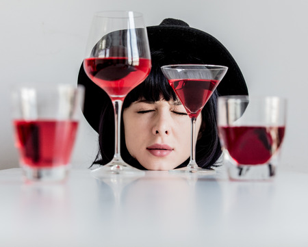 Brunet woman in hat near glasses of wine on white background Imagens
