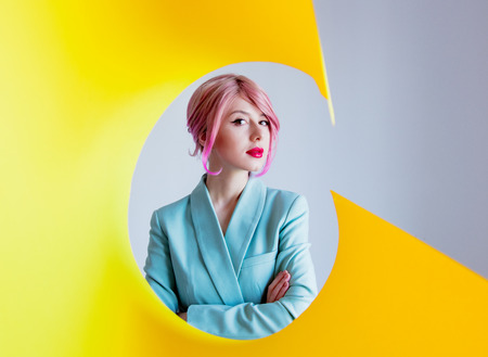 Young girl with pink hair and in blue jacket with yellow paper on foreground