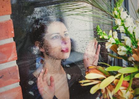 joven mujer triste en la ventana mojada después de que la lluvia pierde las plantas de pie fuera de la ventana.