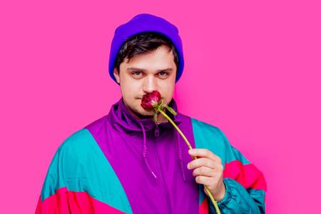 Young man in 90s clothes sniffs blossom peony flower on pink background.