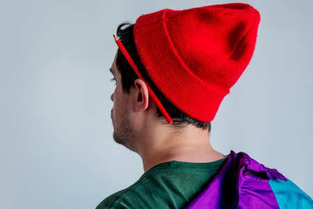 Style man in red hat and trendy clothes with pencil on ear. Back side view 写真素材