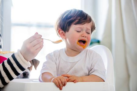 La joven madre intenta alimentar a un niño pequeño con una cuchara en una silla