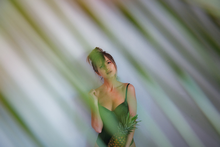 Female in green swimsuit holding pineapple with palm leaves out of focus on grey background Фото со стока - 122806206