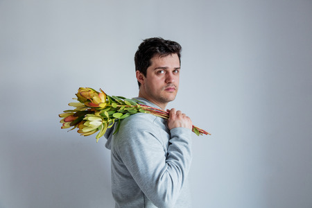 handsome man with sunset safari flower on gray background