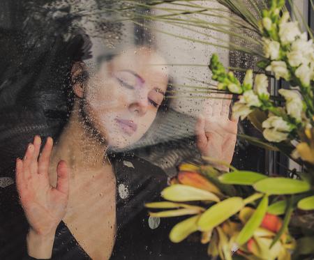 jeune femme triste à la fenêtre humide après la pluie manque les plantes debout devant la fenêtre.