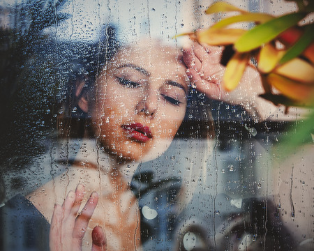 young sad woman at the wet window after the rain misses the plants standing outside the window.