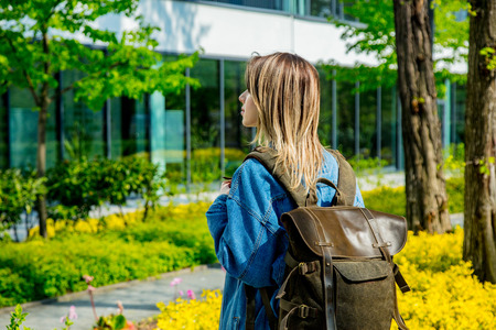 A young student with a backpack is the first time near campus of the university.