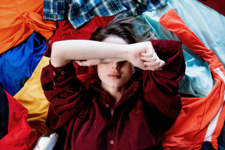 Upset woman keep hands over head and lying on clothes. Above view