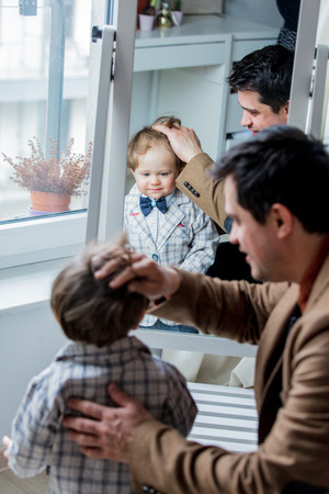 Father dressing up a toddler boy near window at home 版權商用圖片