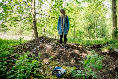 Mujer joven con mochila cerca de la basura en un bosque mixto Beskidy en Polonia en primavera.