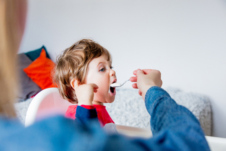 Mother feeds a little toddler boy with a spoon during lunch in the room.