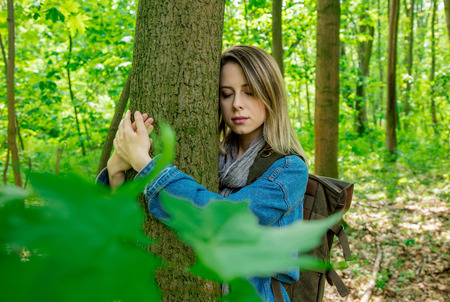 Young woman with backpack hugging a tree in a mixed forest Beskidy in Poland in spring time.