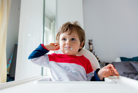 Little toddler boy sitting in a chair for feeding in a room in breakfast time