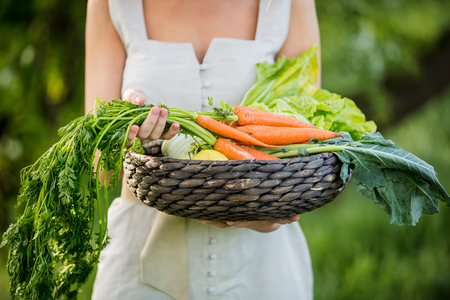 Young woman with vegetable basket at spring time outdoor Standard-Bild - 122874844