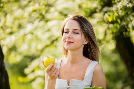 Jeune femme à la pomme au printemps en plein air Banque d'images