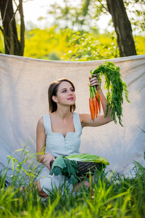 Young woman with vegetables sits near the trees Stockfoto