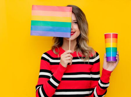 Young woman in red striped sweater with cup and LGBT flag on yellow background