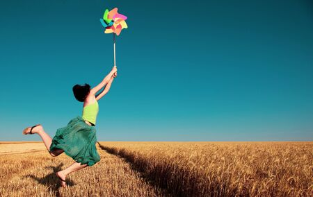 Young girl jumping with pinwheel over wheat field