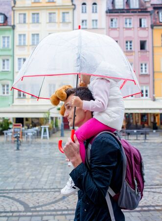 Little girl with umbrella sits on her fathers shoulders