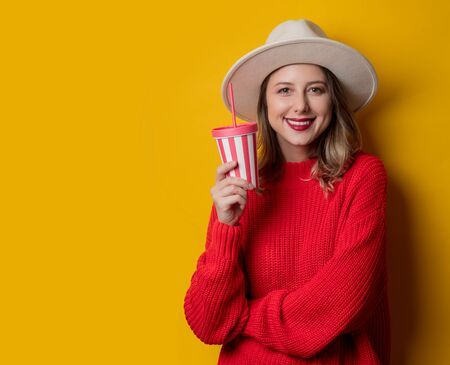 woman in hat and red sweater with drink