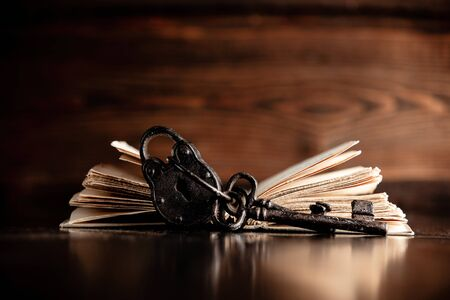 Old book and key on wooden table