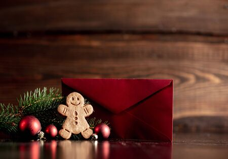 Gingerbread man and Christmas tree with red envelope on wooden table Stock Photo