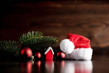 Santa hat and little house on wooden table and background