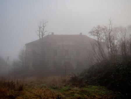 old abandoned manor in the fog in December