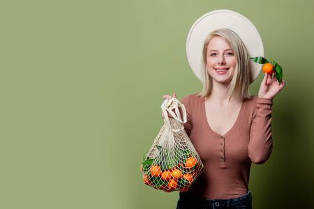 Young woman with mandarins in a string bag Stok Fotoğraf