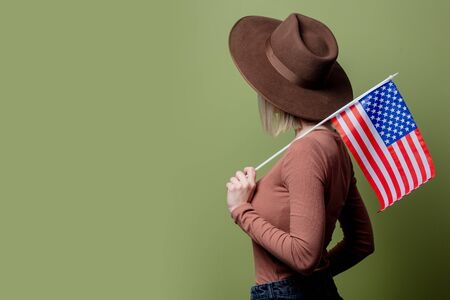 Beautiful cowgirl in a hat with United States of America flag on green background