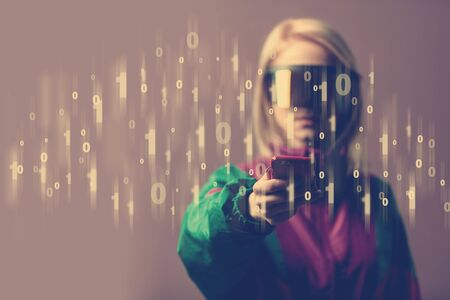 Blonde in VR glasses holds mobile phone with binary code in the foreground