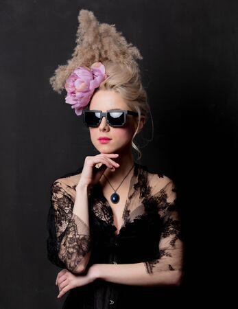 Beautiful blonde countess in sunglasses on dark background