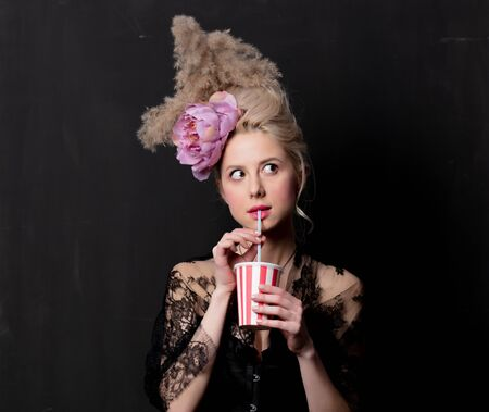Beautiful blonde countess with a drink on dark background
