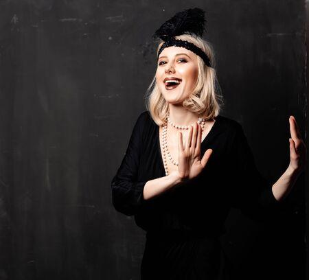 Beautiful blonde woman in twenties years clothes dancing on dark background