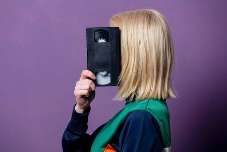Style blonde woman in 80s clothes with VHS on purple background